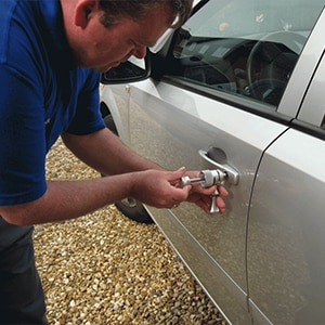 image of a car door lock being picked after the owner locked the keys inside