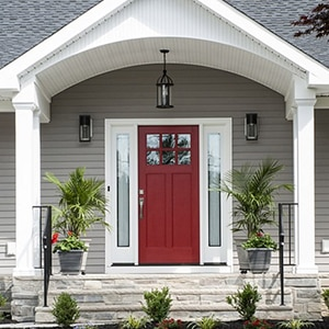 image of a gray house with a red front door